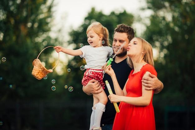 Diversão tempo familiar enquanto soprando bolhas de sabão
