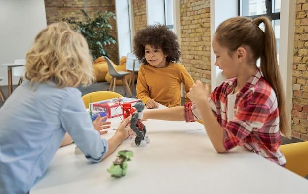 Diversas crianças examinam olhando para brinquedos técnicos em uma mesa cheia de detalhes enquanto têm