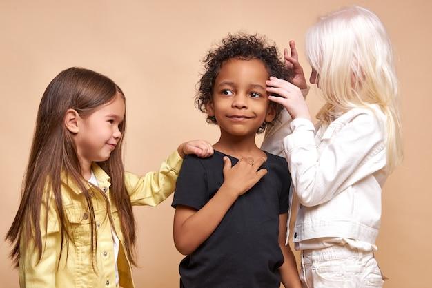 Diversas crianças sorridentes e positivas posando felizes juntas