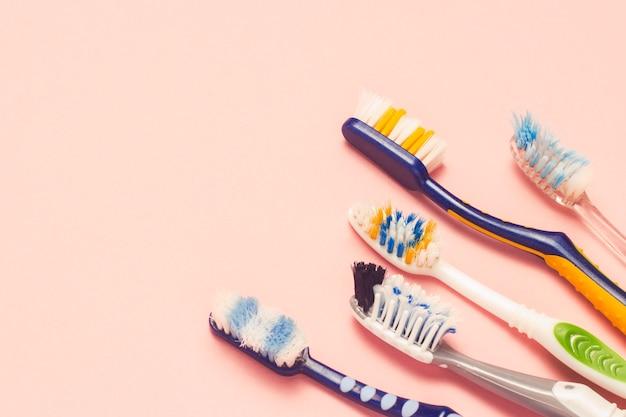 Diversas escovas de dentes usadas diferentes em um fundo rosa. escova de dentes mudar conceito, higiene bucal, família grande e amigável, seleção de escova de dentes. vista plana leiga, superior.