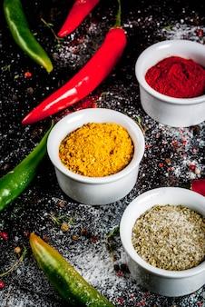 Diversas especiarias e condimentos. cozinhando . açafrão, curry, pimentão, pimenta, pimentão, manjericão seco, sal, pimentão fresco, tomilho. metal enferrujado preto. .