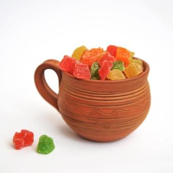 Diversas frutas cristalizadas em uma panela de barro