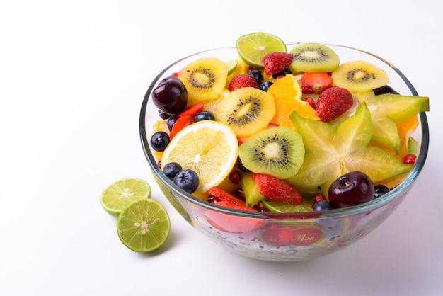Diversas frutas deliciosas servidas em uma tigela de vidro isoladas