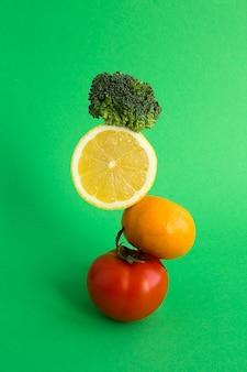 Diversas frutas e vegetais empilhados em pirâmide verde