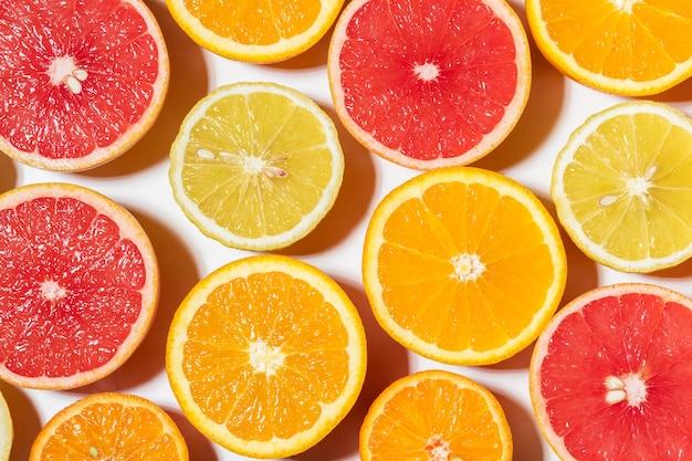 Diversas frutas fatiadas na superfície branca.