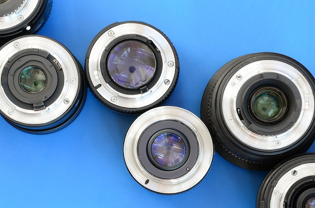 Diversas lentes fotográficas encontram-se em um fundo azul brilhante. espaço para texto