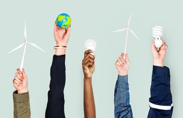 Diversas mãos segurando objetos de energia sustentável
