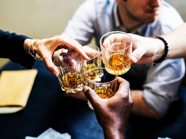 Diversas mãos tinindo copos de álcool