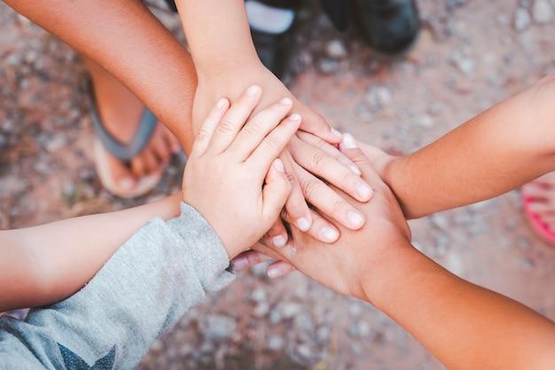 Diversas mãos unidas a partir do conceito de trabalho em equipe de parceria de amizade de mão de criança