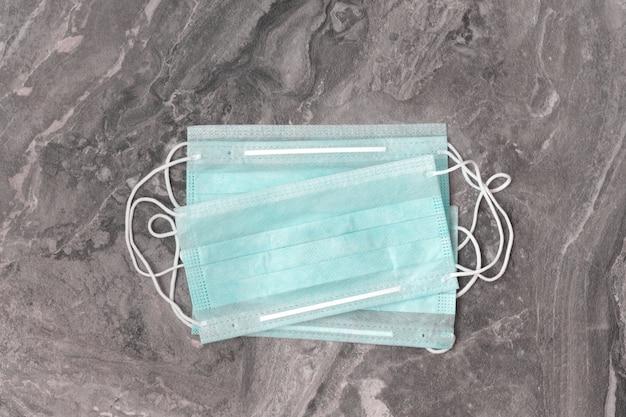 Diversas máscaras verdes médicas protetoras contra o coronavírus ncov-19 em um fundo cinza. serve para prevenir uma epidemia.