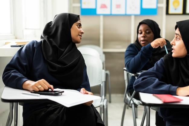 Diversas meninas muçulmanas estudando em sala de aula
