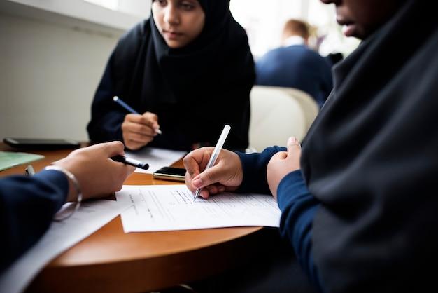 Diversas meninas muçulmanas estudando em uma sala de aula