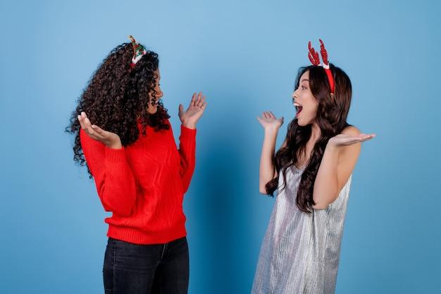 Diversas mulheres caucasianas e negras usando aros de férias isoladas sobre azul