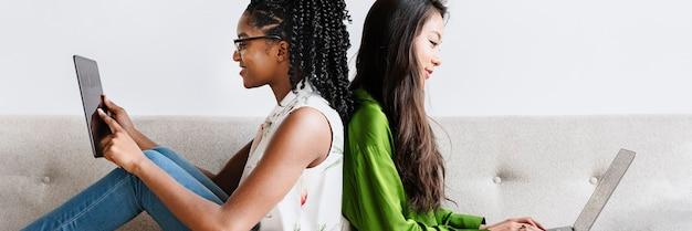 Diversas mulheres sentadas juntas usando dispositivos digitais