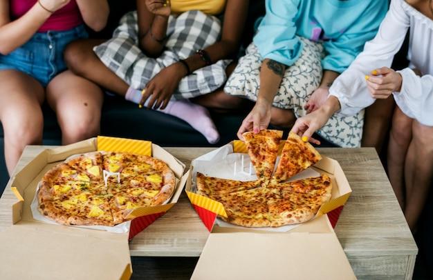 Diversas mulheres sentadas no sofá comendo pizza juntos