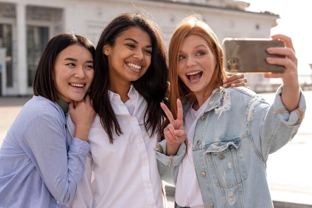 Diversas mulheres tirando uma selfie juntas