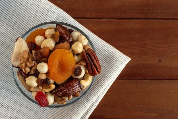 Diversas nozes e frutas secas em uma tigela sobre tecidos de linho. vista superior, espaço para texto