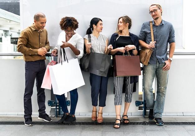 Diversas pessoas com sacolas de compras