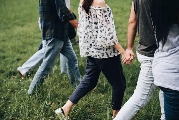 Diversas pessoas de mãos dadas e correndo no parque