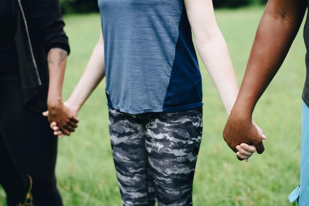 Diversas pessoas de mãos dadas no parque