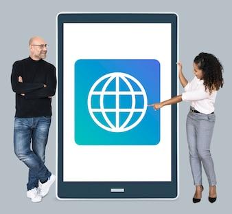 Diversas pessoas em pé ao lado de um tablet com www ícone
