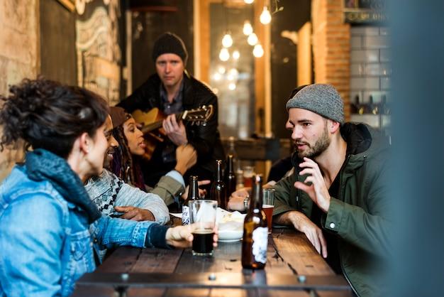 Diversas pessoas penduram para fora da amizade pub