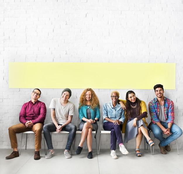 Diversas pessoas que sentam o conceito alegre da parede