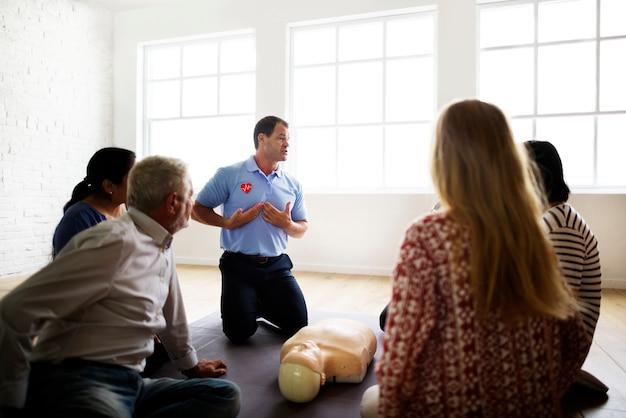 Diversas pessoas que tomam uma aula de treinamento de primeiros socorros cpr