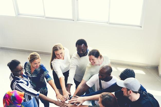 Diversas pessoas se unindo como uma equipe