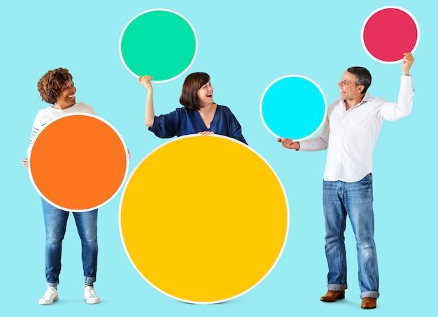Diversas pessoas segurando círculos em branco coloridos