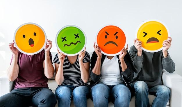 Diversas pessoas segurando emoticon