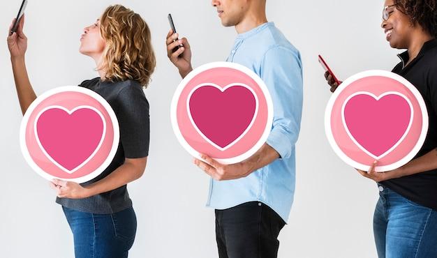 Diversas pessoas segurando ícones dos namorados
