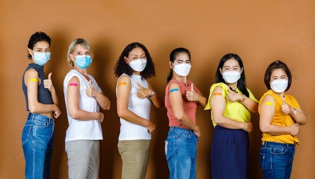Diversas pessoas, seis pacientes multinacionais étnicas do sexo feminino usam máscara facial em pé em ordem de altura, olham para a câmera mostrando polegares para cima com emplastros coloridos juntos após a vacinação contra o coronavírus