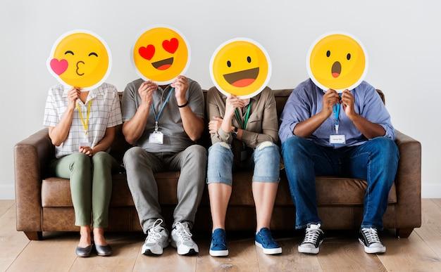 Diversas pessoas sentadas e cobrindo o rosto com placas de emojis