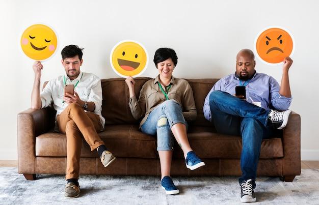 Diversas pessoas sentadas e segurando logotipos de emojis