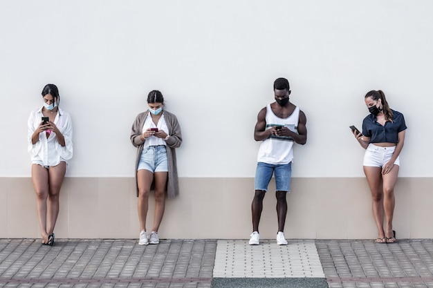 Diversos amigos navegando em smartphones na rua