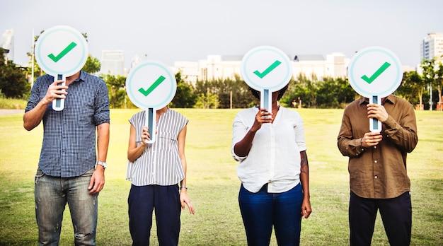 Diversos amigos segurando ícones de marca de seleção