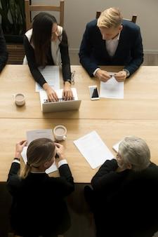 Diversos colegas de trabalho trabalhando juntos na reunião, vista superior vertical