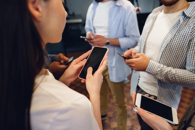Diversos colegas jovens trabalhando juntos em telefones celulares no escritório