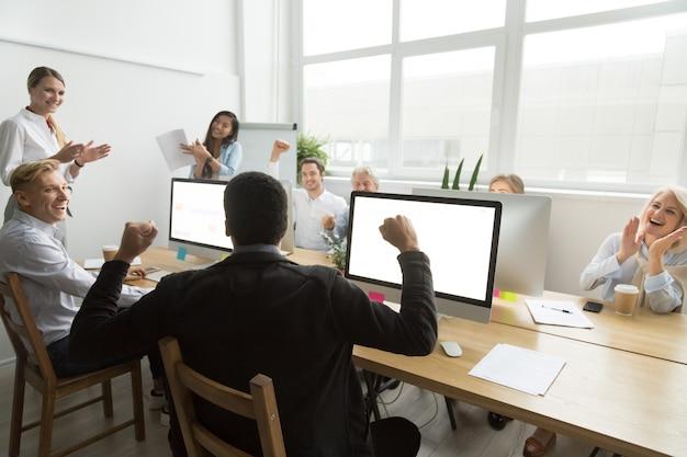 Diversos colegas parabenizando colega de trabalho negra com bom resultado ou ganhar