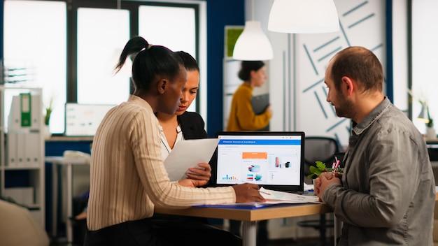 Diversos empresários, grupo de funcionários da empresa, sentados à mesa em um escritório moderno, discutindo sobre problemas financeiros, sentado à mesa, trabalhando no computador laptop no local de trabalho corporativo.