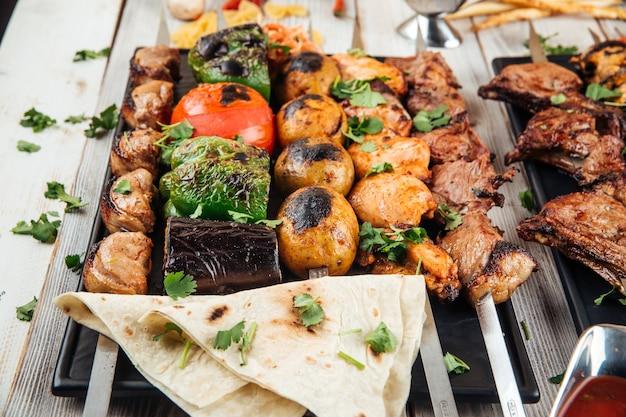 Diversos espetos caucasianos shashlyq com carne e vegetais