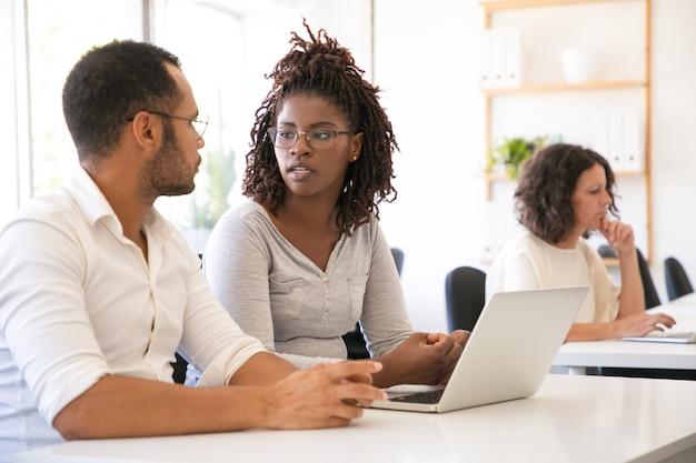 Diversos estudantes sentados na mesa com o laptop