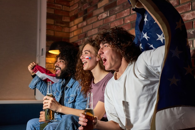 Diversos fãs de esportes comemoram a vitória em casa. apoiadores apaixonados gritam assistindo jogo na tv, torcendo juntos, gritando emocionalmente