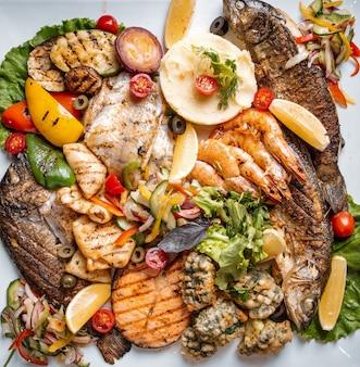 Diversos frutos do mar servidos com peixe camarão e calamar