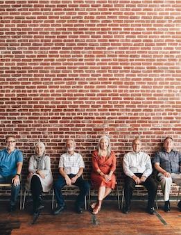 Diversos idosos sentados em uma fileira contra uma parede de tijolos