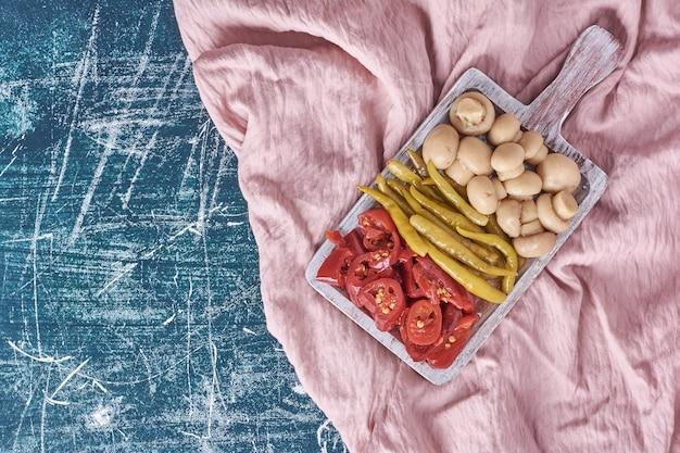 Diversos legumes em conserva na chapa branca com toalha de mesa.