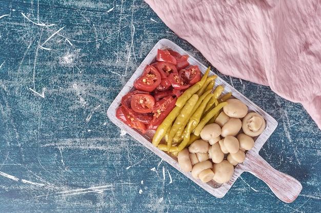 Diversos legumes em conserva na chapa branca com toalha de mesa. Foto gratuita