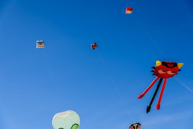 Diversos papagaios dos jogos das crianças de verão que voam no céu azul.