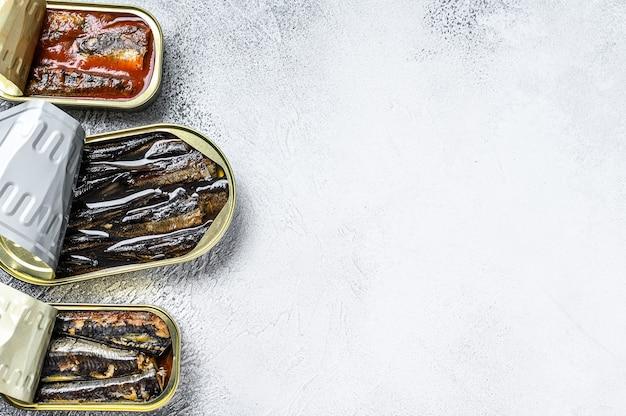 Diversos peixes enlatados em lata de sardinha, sardinha defumada, cavala. fundo cinza de madeira. vista do topo. copie o espaço.